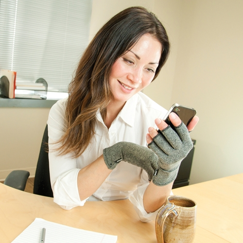 Woman wearing IMAK compression arthritis gloves while using her smartphone.