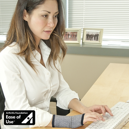 Woman types on a keyboard in an office while wearing an IMAK Compression wrist sleeve.