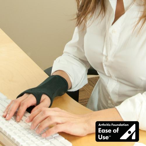 Photo of woman wearing the Brownmed IMAK RSI SmartGlove while typing.