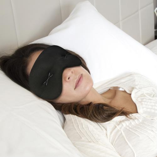 Woman wearing an IMAK Eye Pillow sleep mask.